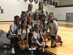 8th grade Lady Dragons volleyball team posing in front of a trophy